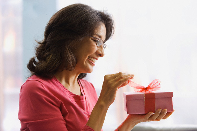 West New York, New Jersey, USA --- Hispanic woman opening gift --- Image by © Jose Luis Pelaez, Inc./Blend Images/Corbis